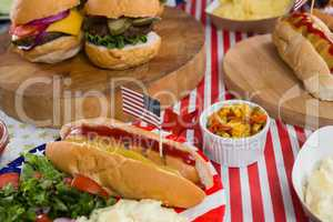 Burgers and hot dogs on wooden table with 4th july theme