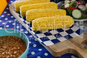 Baked beans and corn cob on wooden table with 4th july theme