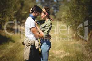 Young couple embracing at olive farm on sunny day