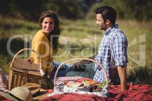 Portrait of young woman sitting with boyfriend on picnic blanket