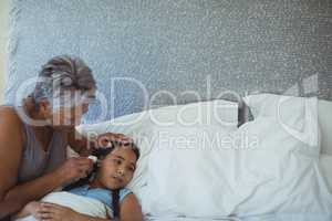 Grandmother checking body temperature of sick granddaughter in bed room