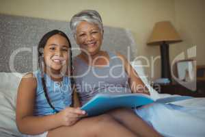Grandmother and granddaughter holding photo album in bed room