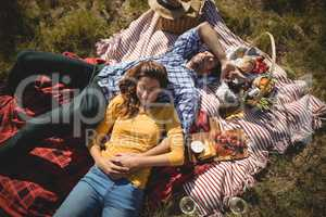 High angle view of young couple resting together on picnic blanket