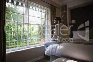 Man sitting on bed by window in bedroom