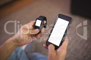 Man using smart watch and mobile phone in living room