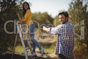 Portrait of man photographing girlfriend at olive farm