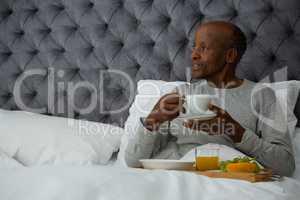 Senior man looking away while having breakfast on bed