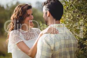 Young couple by olive tree on sunny day at farm