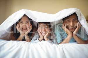 Family relaxing together under a blanket in bedroom