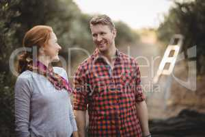 Couple looking at each other while standing at olive farm
