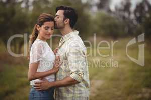 Young couple romancing on field at farm