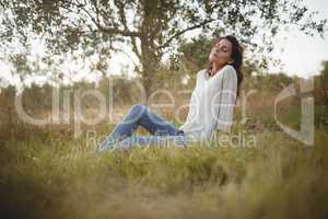 Young woman resting on grassy field at farm