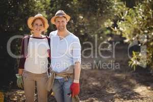Happy couple standing at olive farm on sunny day