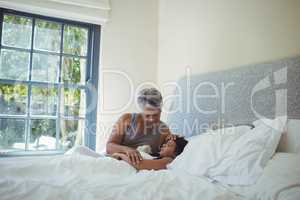 Grandmother comforting sick granddaughter in bed room