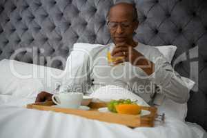Senior man having breakfast on bed at home