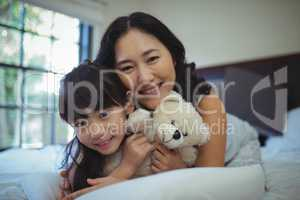 Mother and daughter relaxing on bed in bed room