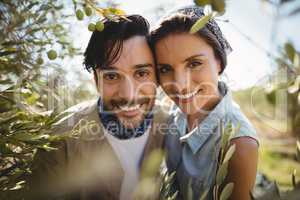 Portrait of smiling young couple by olive trees at farm