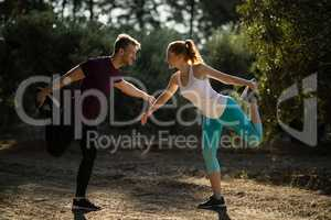 Full length of young couple exercising on field at farm