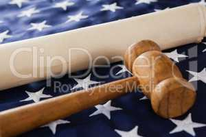 Gavel and rolled-up document arranged on American flag