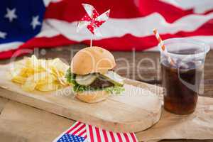 Burger and cold drink on wooden board