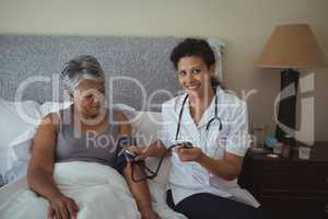Female doctor measuring blood pressure of a senior woman