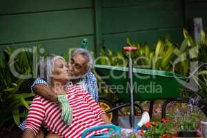 Senior man kissing smiling woman in backyard