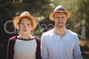 Young couple wearing hat on sunny day at farm