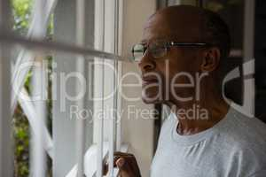 Thoughtful senior man wearing eyeglasses while looking out through window