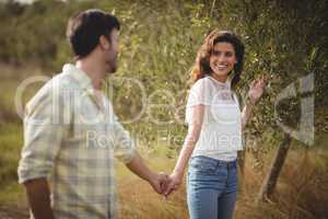 Smiling couple standing by tree at farm