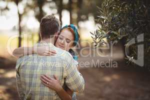 Couple embracing by olive tree at farm