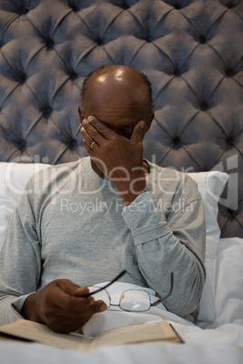 Tired senior man massaging his eyes while holding eyeglasses on bed
