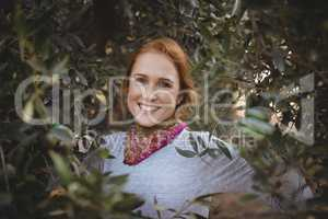Smiling young woman standing amidst trees at olive farm