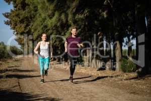 Full length of young couple jogging at farm