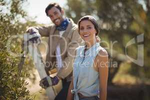 Happy young couple standing by trees at olive farm
