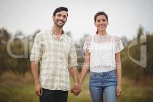 Smiling young couple holding hands at olive farm
