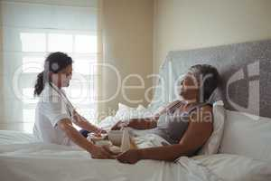 Female doctor serving breakfast to senior woman on bed