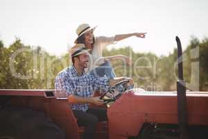 Cheerful woman gesturing away while sitting with boyfriend on tractor