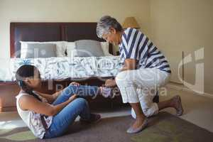 Grandmother helping granddaughter to wear shoes in bed room