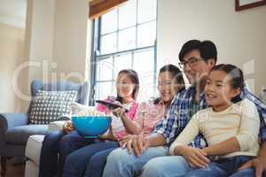 Smiling family watching television together in living room