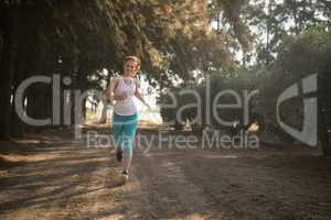 Smiling young woman jogging on dirt road during sunny day