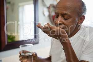 Senior man taking medicine in bathroom