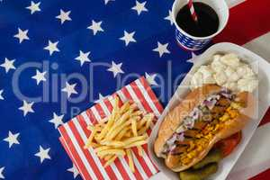 Hot dog served on plate with french fries and cold drink