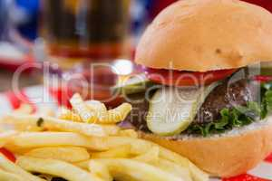 Burger and french fries on wooden table with 4th july theme
