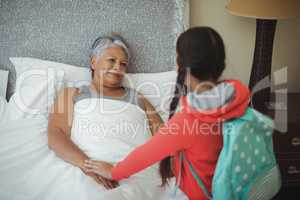 Granddaughter comforting sick grandmother in bed room