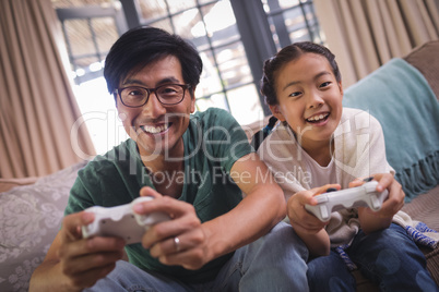 Father and daughter playing video game in living room