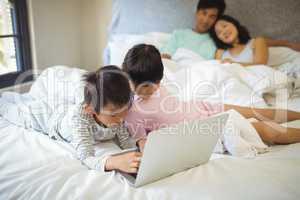 Sibling using laptop in bedroom