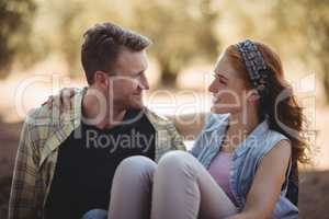 Smiling young couple sitting on field at olive farm