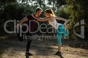 Full length of young man and woman exercising on field at farm