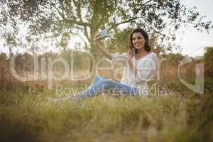 Beautiful woman taking selfie while sitting on grassy field