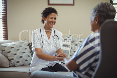 Female doctor comforting senior woman in living room